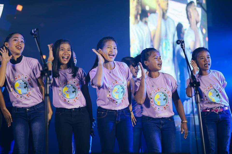 The kids singing their hearts out on stage.